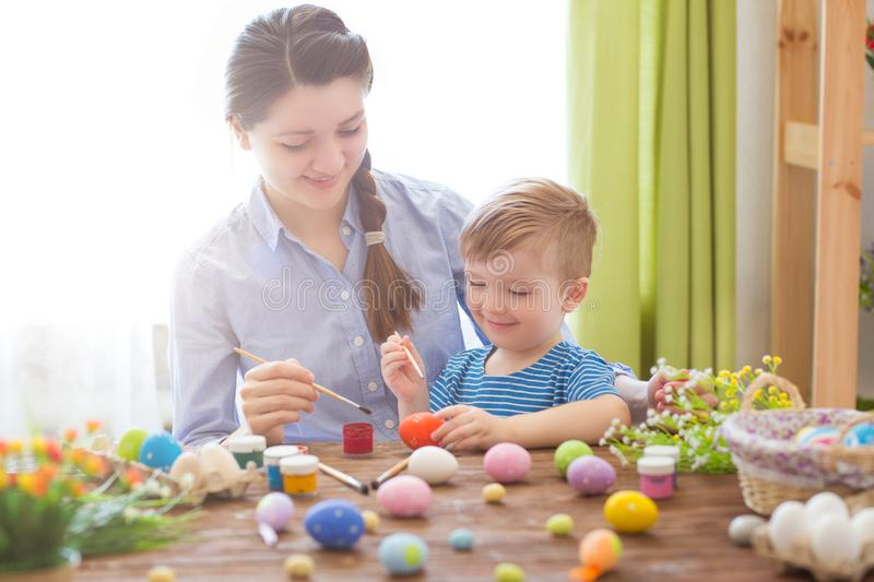 Easter concept. Happy mother and her cute child getting ready for Easter by painting the eggs stock photos