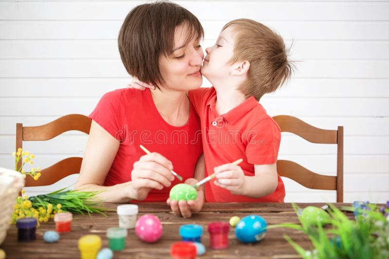 Easter concept. Happy mother and her cute child getting ready for Easter by painting the eggs. Happy family Mom and children son royalty free stock photos