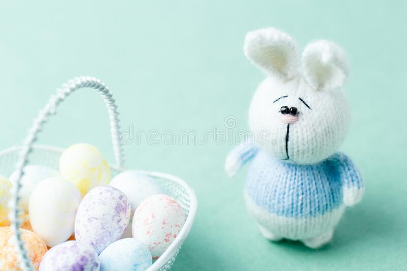 Easter concept. Knitted bunny staying near basket with eggs royalty free stock photo