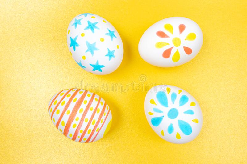 Easter concept. White eggs with marker drawings. Easter concept. White eggs with marker simple children`s drawings. Manual coloring. Yellow, blue and red shades stock image