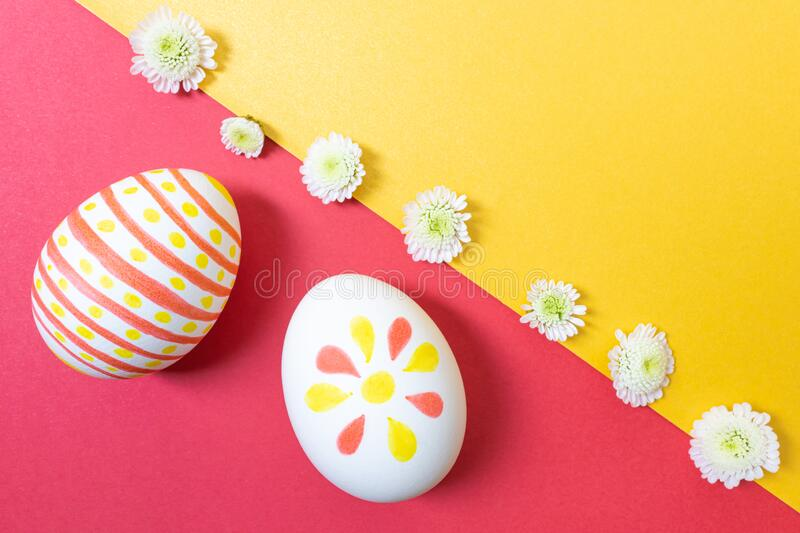 Easter concept. White eggs with marker drawings. Easter concept. White eggs with marker simple children`s drawings. Manual coloring. Yellow and red shades stock photo