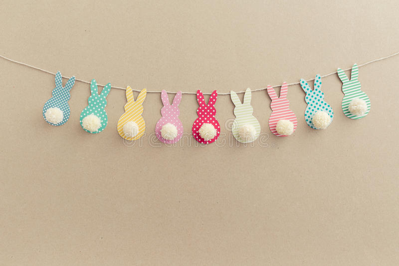 Easter Crafts. Easter Bunny Banner. Cute bunny shapes with yarn pom pom tails royalty free stock photo