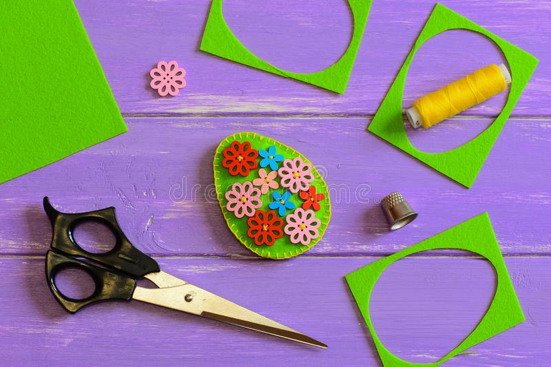Felt Easter egg crafts. Felt Easter egg decor with colorful wooden flower buttons. Felt scrap, scissors, thimble, thread. Easter crafts for elementary students stock image