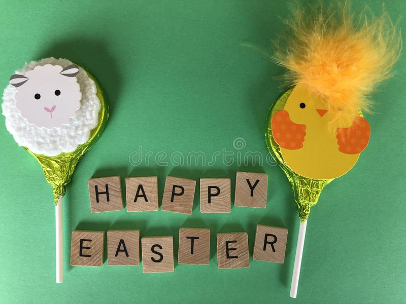 Easter, creative concept, with room for text. Happy Easter in wooden letters with two chocolate lollipops, a fluffy lamb and an Easter chick isolated on a green stock photography