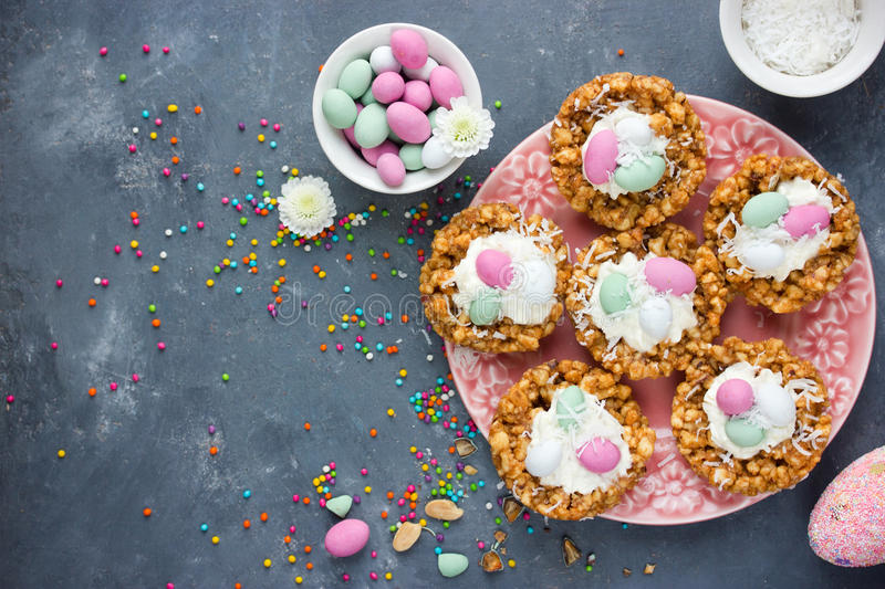 Easter crispy nest cakes. With chocolate candy eggs and whipped cream royalty free stock photography