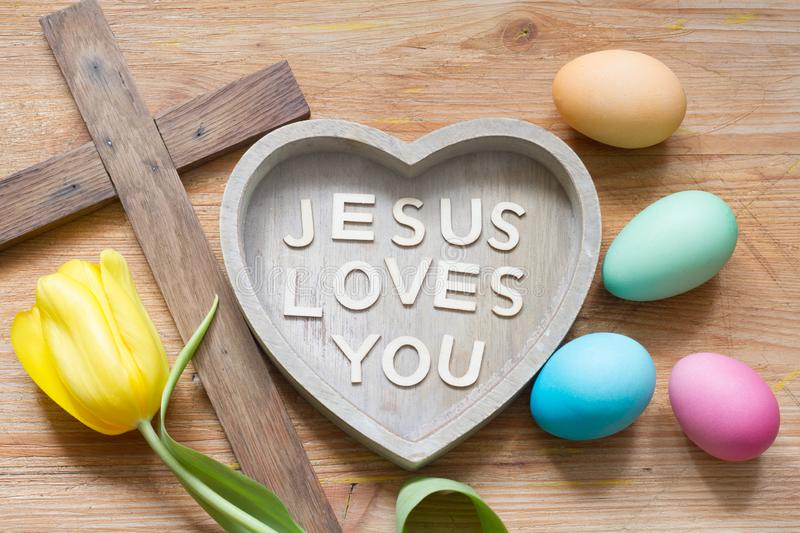 Easter cross and heart with inscription Jesus loves you on abstract wooden spring board royalty free stock photos