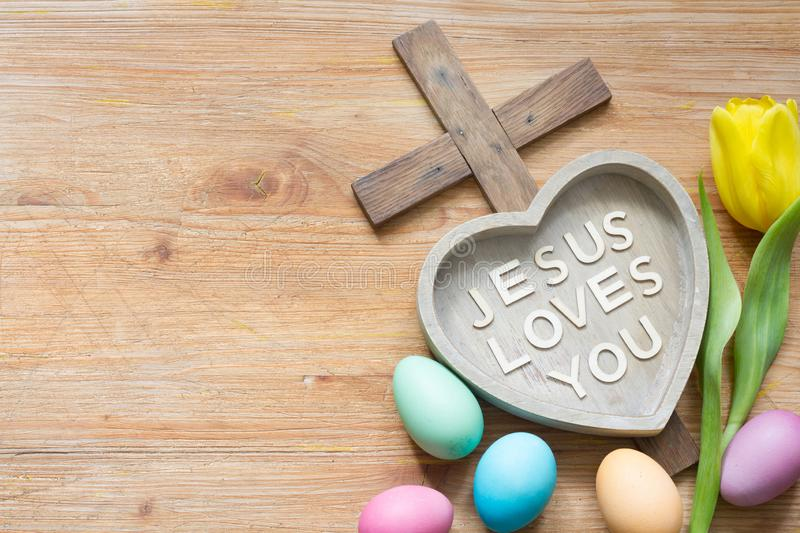Easter cross and heart with inscription Jesus loves you on abstract wooden spring board royalty free stock photography