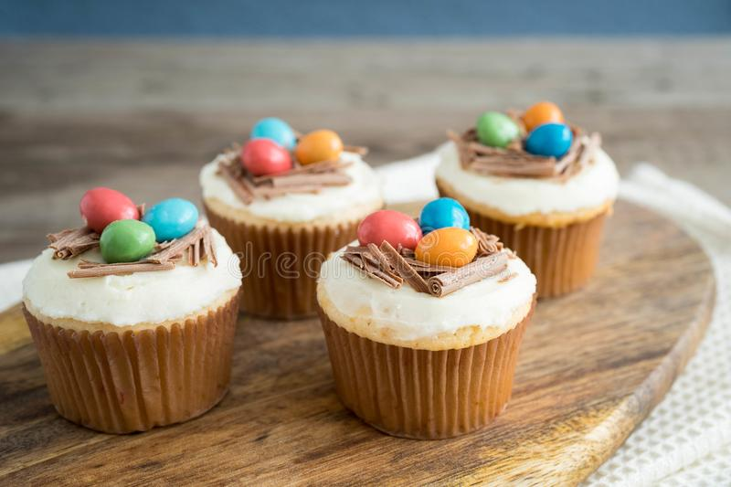 Easter cupcakes with chocolate frosting and candy eggs stock images