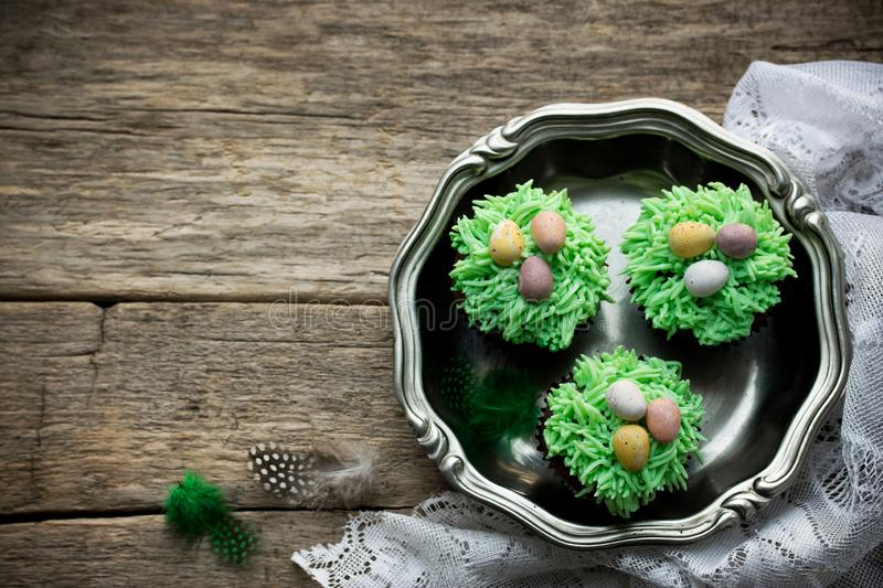 Easter cupcakes eggs on green grass stock photo