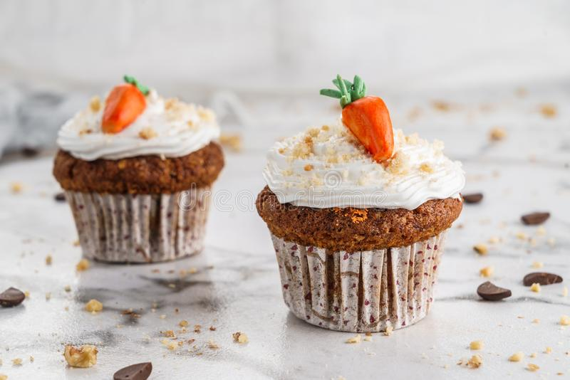 Easter cupcakes or muffins with cream and carrot candy on light marble background. Holiday cake celebration, delicious dessert, royalty free stock image
