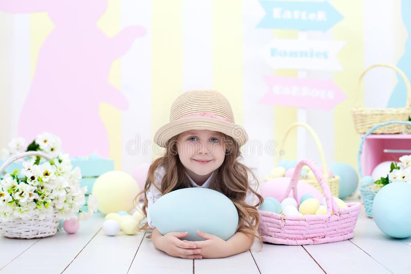 Easter! Cute girl playing with easter egg. A child holds a large colorful egg on the background of Easter interior. Easter colorfu stock photography