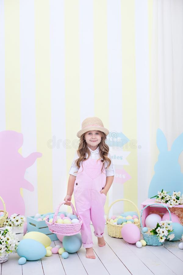 Easter! A cute girl is standing and holding a basket with eggs in her hands with a decoration in the background. Cute girl hunts f. Or Easter eggs. Easter decor stock images