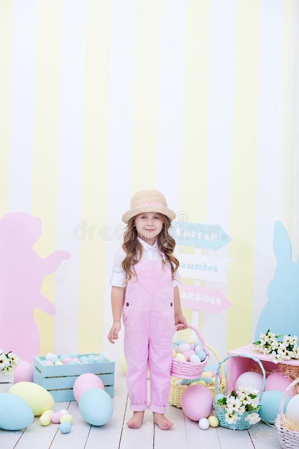 Easter! A cute girl is standing and holding a basket with eggs in her hands with a decoration in the background. Cute girl hunts f. Or Easter eggs. Easter decor stock photos