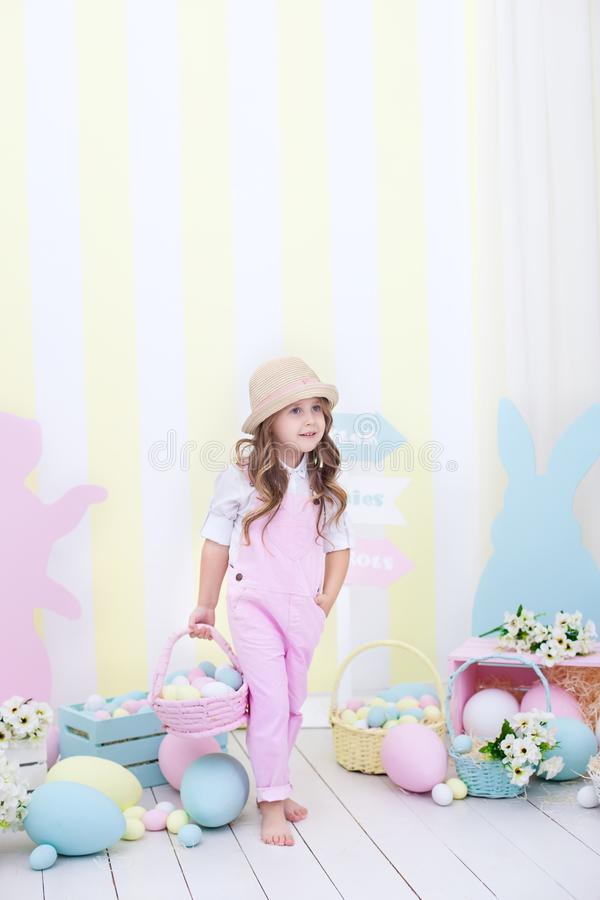 Easter! A cute girl is standing and holding a basket with eggs in her hands with a decoration in the background. Cute girl hunts f. Or Easter eggs. Easter decor royalty free stock photo