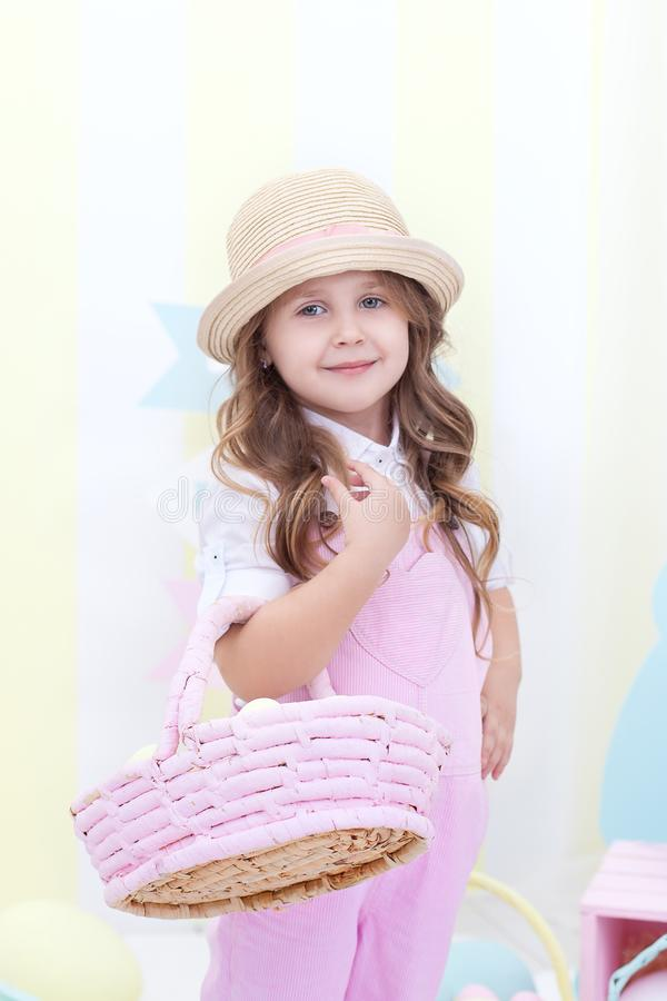 Easter! A cute girl is standing and holding a basket with eggs in her hands with a decoration in the background. Cute girl hunts f. Or Easter eggs. Easter decor stock photo