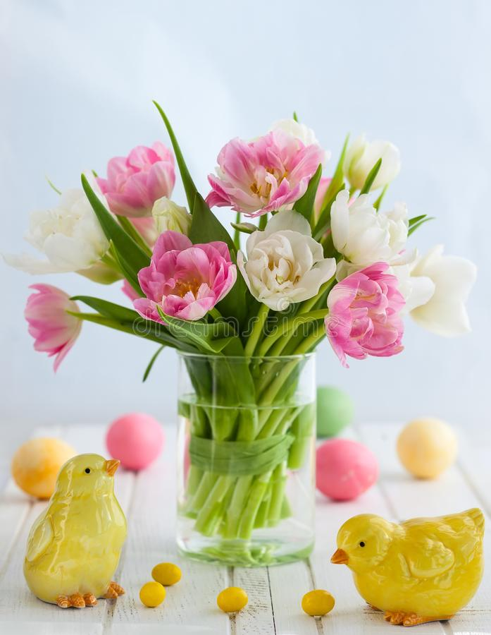 Easter decor. Easter bouquet of spring tulips and Easter decor on white wooden table. Easter concept with copy space stock images