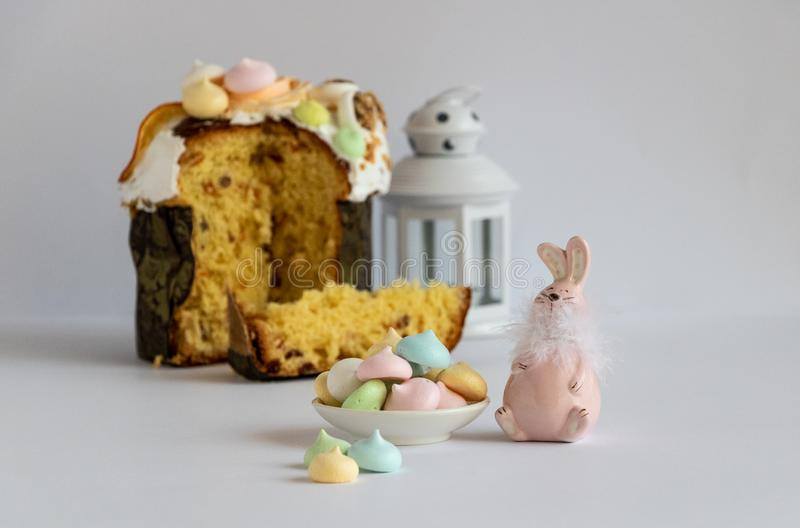 Easter decor with colorful meringues, Easter cake and a pastel pink color bunny. stock photography