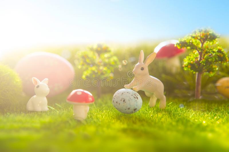 Easter decorate with rabbit toy and easter eggs on grass field background royalty free stock photo