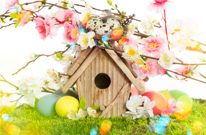 Easter decoration with birdhouse and eggs. Spring blossoms. Easter decoration with birdhouse and eggs on green grass. Spring apple and cherry blossoms. Retro stock image