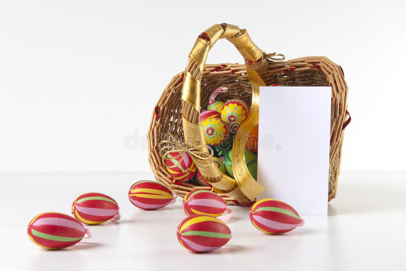 Easter Decoration with blank greeting card. Basket full of Easter eggs scattered on white table with blank greeting card isolated with clipping path. Please see stock photos
