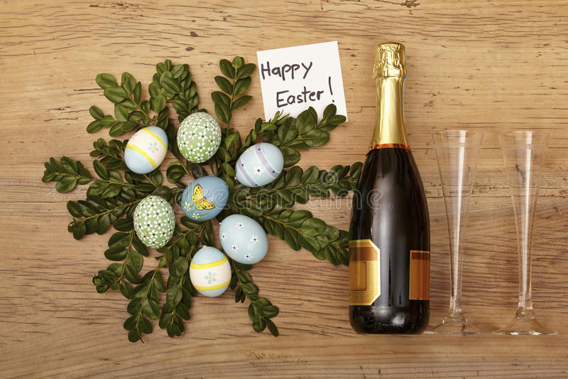 Easter decoration, champagner bootle and champagne glasses on wood stock photography