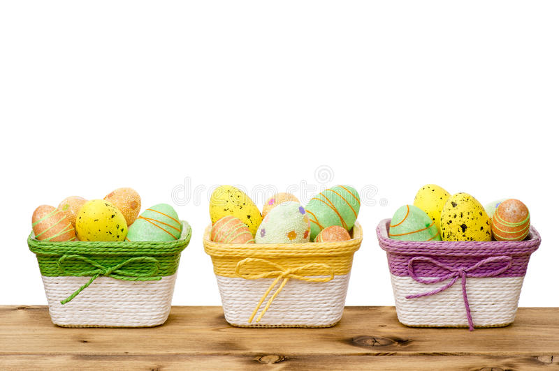 Easter decoration - easter eggs in the colorful baskets on the wooden background. stock photo