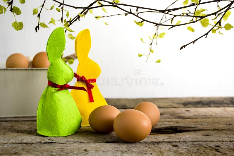 Easter decoration with handmade rabbits and eggs on wooden table and brunches of tree. royalty free stock images