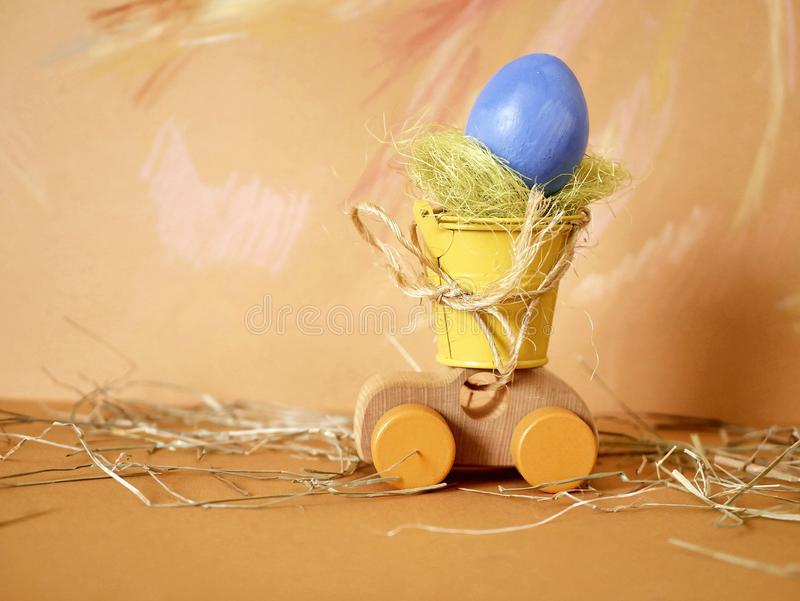 Easter decoration, painted egg, toy wooden car on a bright pastel background stock image