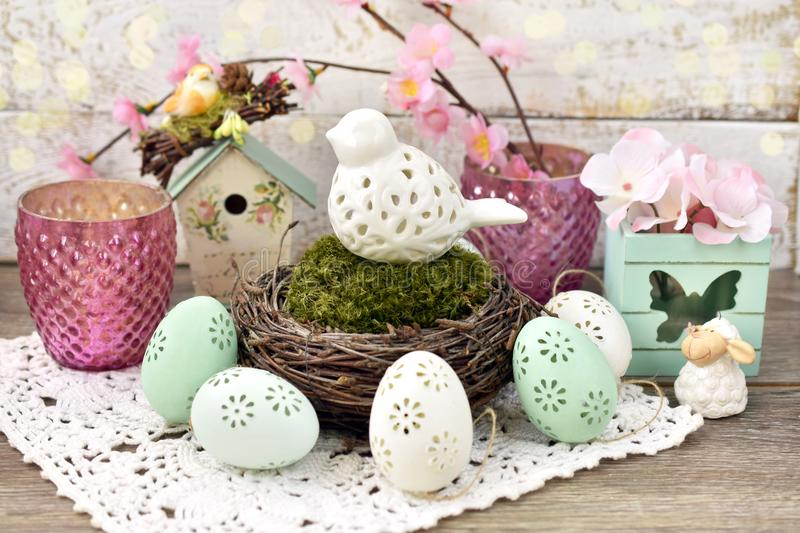 Easter decoration with porcelain bird in nest and eggs. Easter decoration with porcelain bird in nest with moss and eggs royalty free stock image