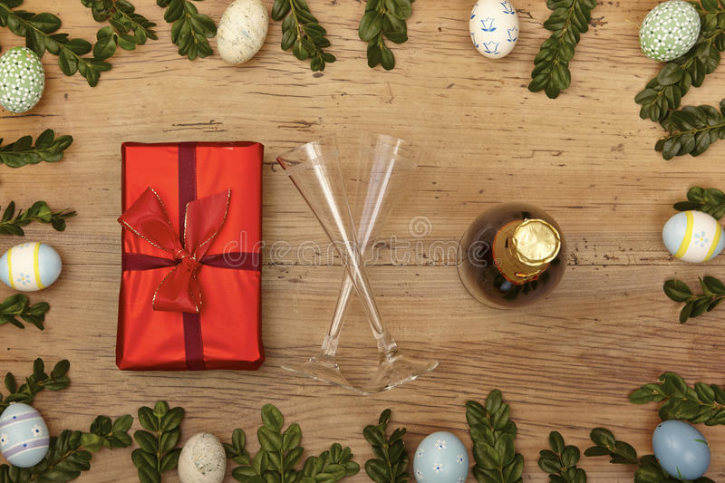 Easter decoration, present, champagner bootle and champagne glasses on wood stock photography
