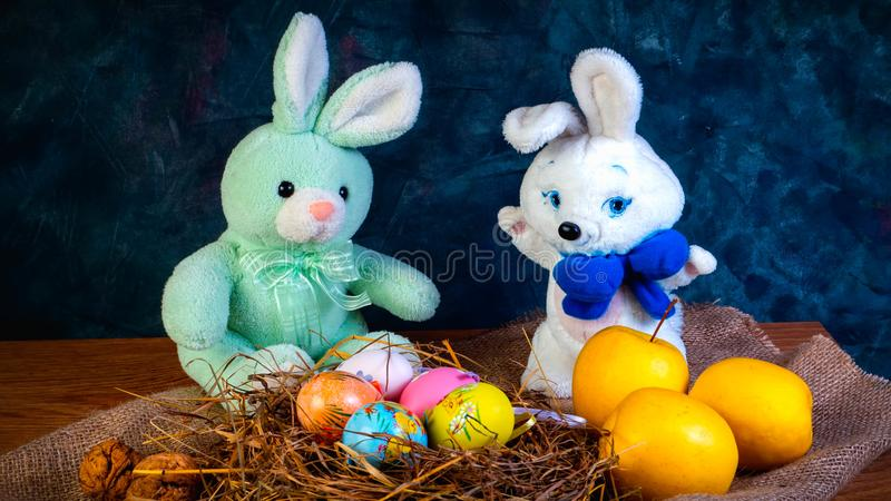 Easter decoration, sweet Easter bunny, rabbits with apple and Easter eggs, on wooden table. stock images