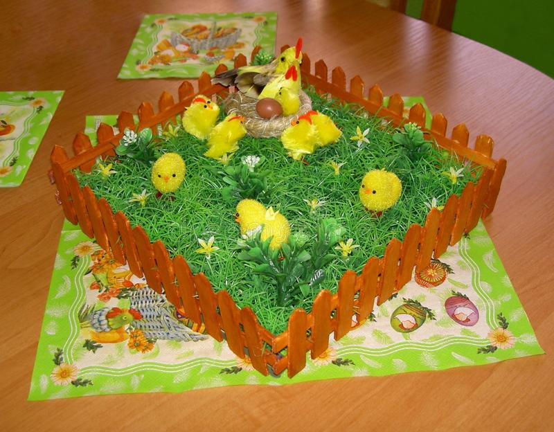 Easter decoration of the table with a napkins and a fence with grass, hen, nest, egg and chickens stock image