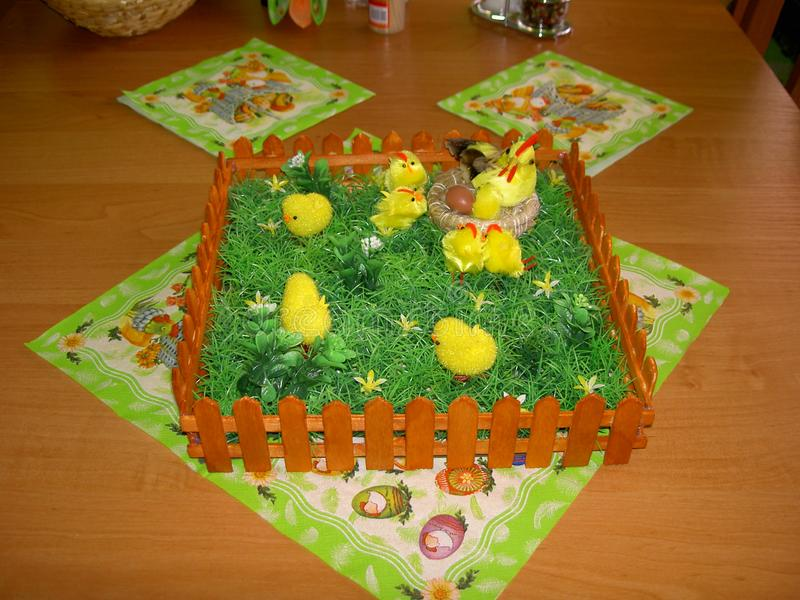 Easter decoration of the table with a napkins and a fence with grass, hen, nest, egg and chickens and next things. Image stock images