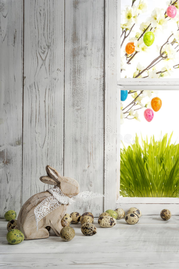 Easter decoration, wooden easter bunny and quail eggs stock photos