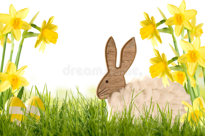 Easter Decoration Wooden Rabbit with Daffodils. On green meadow stock photos