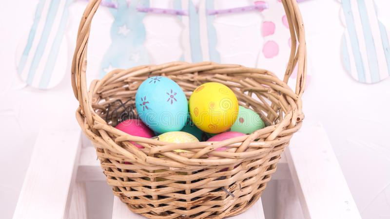 Easter decorations: basket with Easter eggs on a white background royalty free stock image