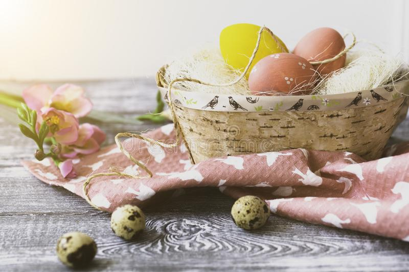 Easter decorations with Easter eggs in a birch bark basket, spring flowers on a gray wooden table stock photos