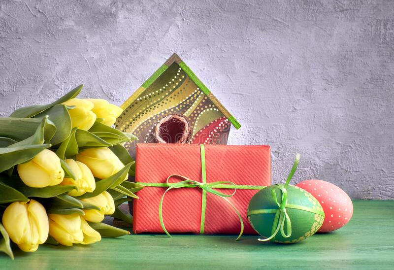 Yellow tulips, birdhouse and painted Easter eggs with wrapped present. Easter decorations on gray concrete background. Yellow tulips, birdhouse and painted stock image
