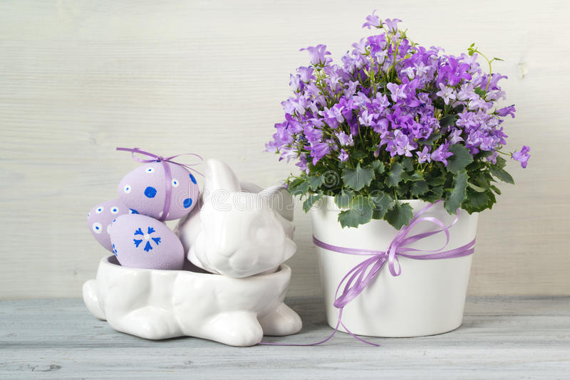 Easter decorations with rabbit full of easter eggs and a pot of spring flowers on a white wooden background. Easter decorations with white rabbit full of easter stock photography