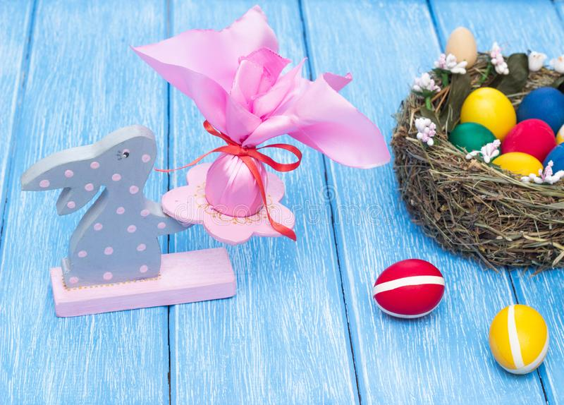 Easter decorative bunny with a festive egg on the background of a nest with multi-colored chicken eggs on a wooden background stock photo