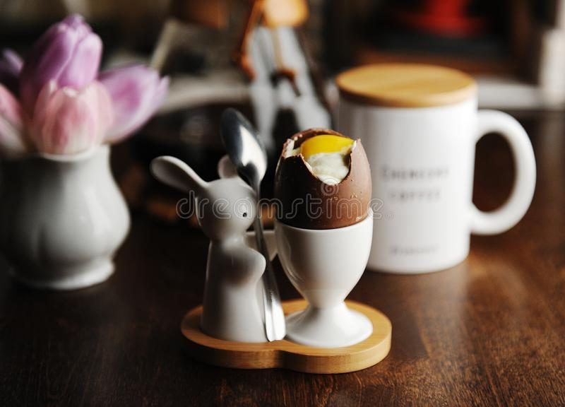 Easter dessert chocolate eggs filled with cream imitating white and yolk. Served on holder with Easter bunny stock images