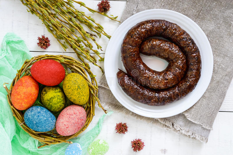 Easter dishes: colorful colored eggs, home-made sausage ring, willow twigs stock image