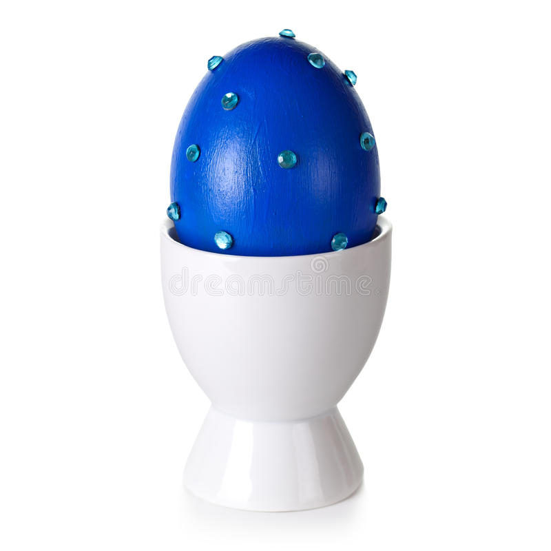 Easter Egg. On stand on white background. Blue eggshell hand decorated royalty free stock images