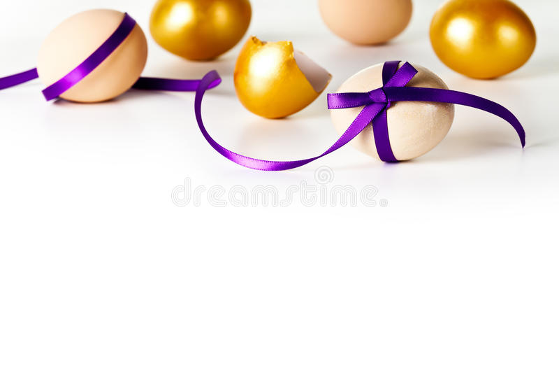 Easter Egg. With violet bow on white background. Composition with beige and gold eggs royalty free stock photography