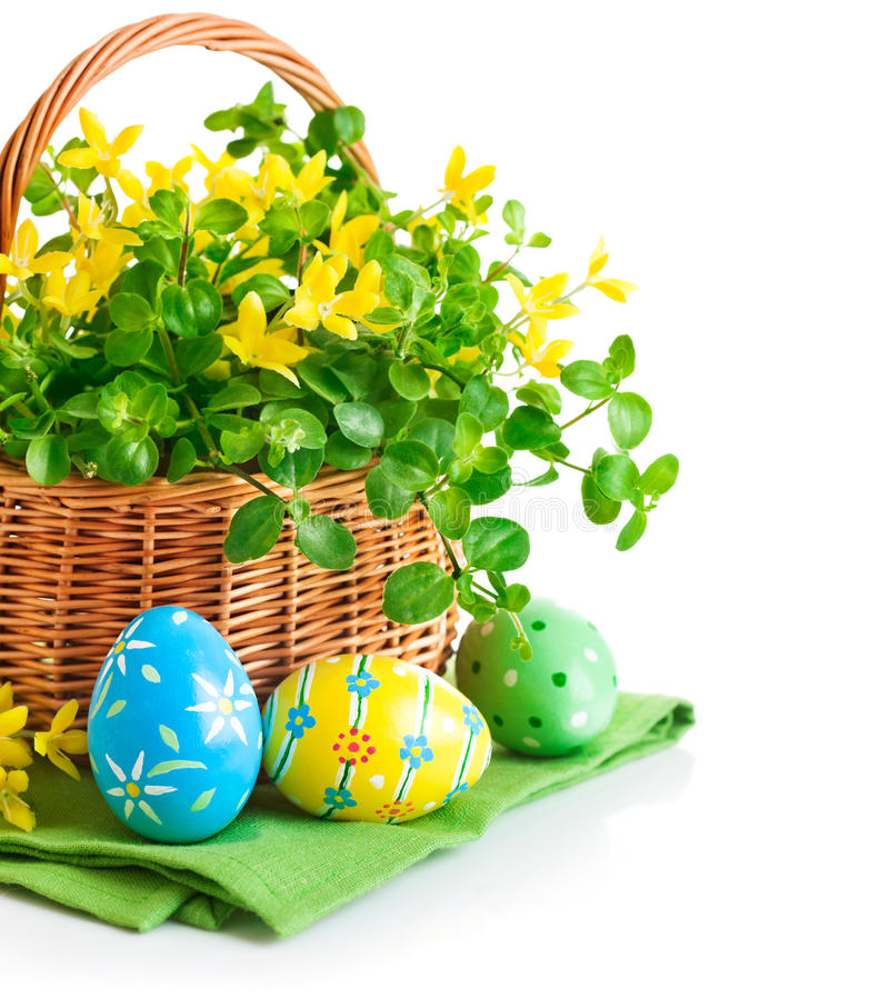 Easter eggs in basket with spring flowers royalty free stock image