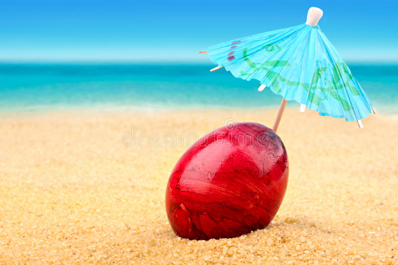 Easter egg at beach. Easter egg with sunshade at the beach royalty free stock photo
