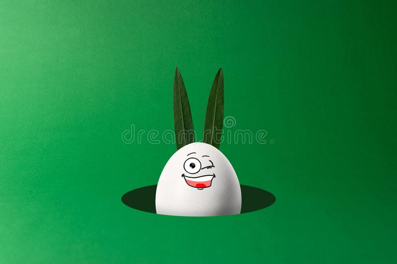 Easter egg with bunny ears and funny face peeking out from hole. Minimal concept.  stock photos