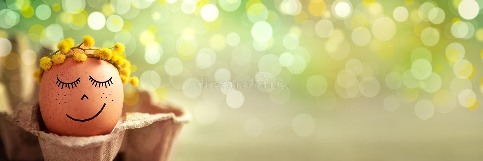Calm and spiritual Easter holiday. Easter egg with calm and spiritual face expression  in springtime bokeh background stock images