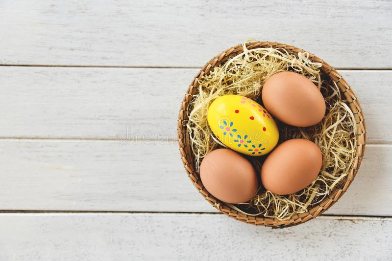 Easter egg and chicken eggs basket nest decoration on white wooden background top view royalty free stock photo