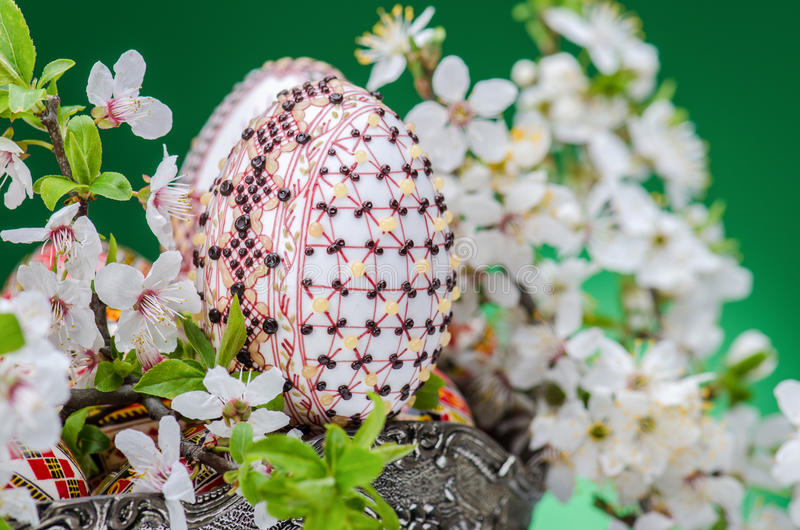 Easter egg. Colorful painted egg in a silver bowl with branches of plum cherry flowers close up against floral background royalty free stock photo